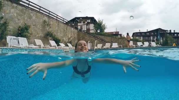 Happy smiling girl swimming in pool