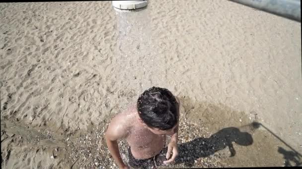 Close up of a young man showering on beach, SLOW MOTION