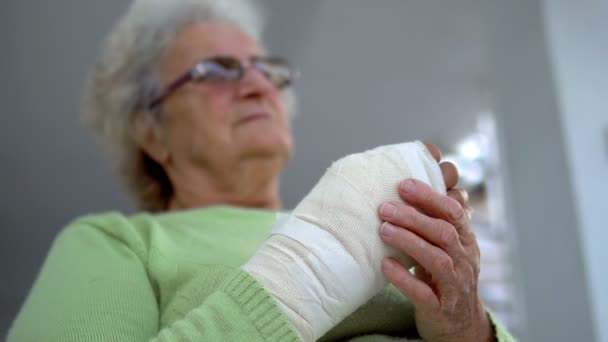 Sad old woman having pain sitting and holding her injured hand in bandages
