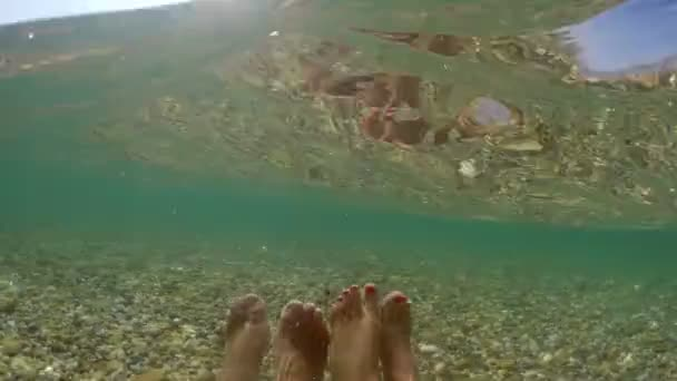 pov of couple feet relaxing in sea shallow water
