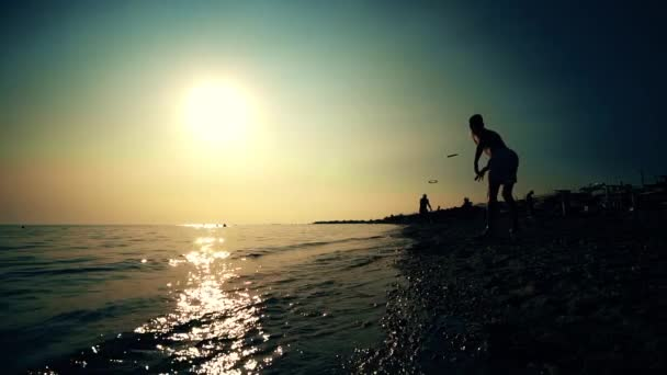Silhouette friends playing frisbee on beach during sunrise or sunset, SLOW MOTION