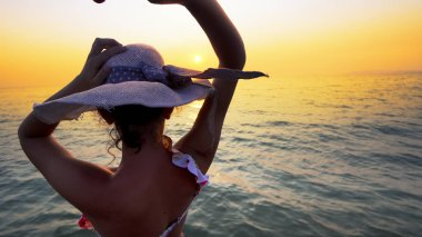 Romantic couple on honeymoon at sunset. Smiling girlfriend with hat walking with holding hand of her boyfriend on the beach. Couple enjoying summer vacation on beach