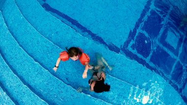 Aerial view of mother and little girl with arm bands relaxing in luxury pool, slow motion