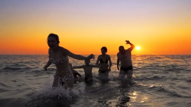 Cinematic shot of family people having fun dancing and running out of ocean water against sunset. cinematic steadicam shot