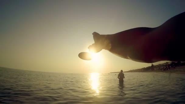 Ruka je házení frisbee disk na pláži na letní západ slunce tónovaný s retro vintage instagram efekt filtru, zpomalené