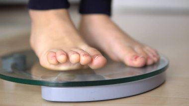woman feet standing on weigh scales, weight loss diet