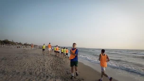 Labdarúgás sport csapat részt jogging képzés tengeren napkeltekor. Thay hogy futni a tenger partján. Steadicamnél lövés