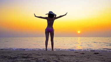 Summer vacation travel concept. Young teen in bikini wearing hat spreading hands outstreched wide open against sea sunset