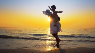 Family having fun on beach on travel vacation summer holidays. Young happy boy and mother doing playful joyful piggybacking ride outdoors at vibrant sunset