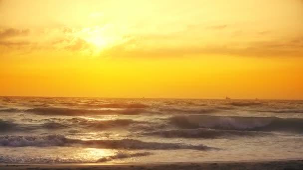 Západ slunce přívalové vlny zřítilo během větrný večer na Atlantický oceán, zpomalené