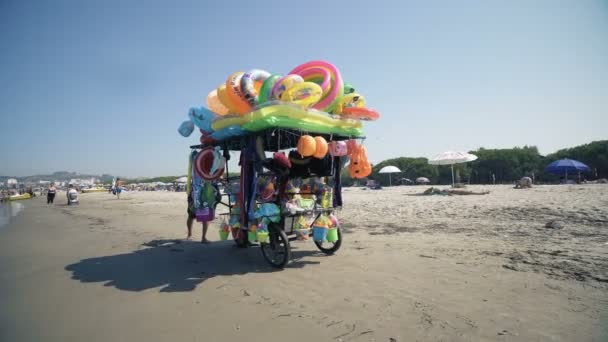 The man ride mobile shop selling toys to child on the beach, cinematic steadicam shot