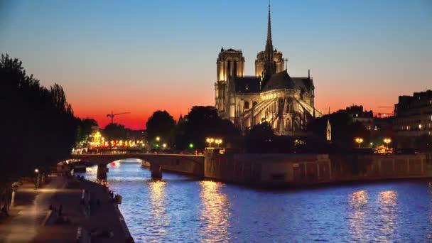A Notre-Dame katedrális és a twilight naplemente, Franciaország, háttér loop Párizsban a Szajna folyón a folyóparti