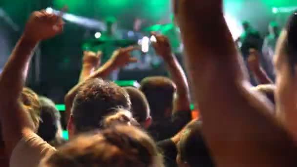 Lidé na koncertě ozářená světla s rukama paintballovém dávnověku. Veřejný koncert, žádná jízdenek událost