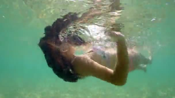 Beautiful mysterious woman with flowing brunette hair swimming on Carebbian water backlit by sun, underwater view