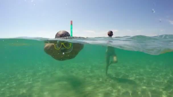 Mann mit Schnorchelmaske schwimmt im Sommerurlaub unter Wasser auf Kamera zu