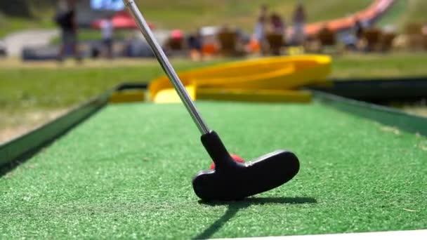 Hra mini golf, filmový pohled. Golfový míček a golfového klubu na umělé trávě