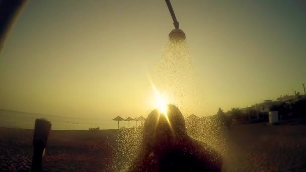 Man take shower in the open air on the beach in the light of sunset, SLOW MOTION