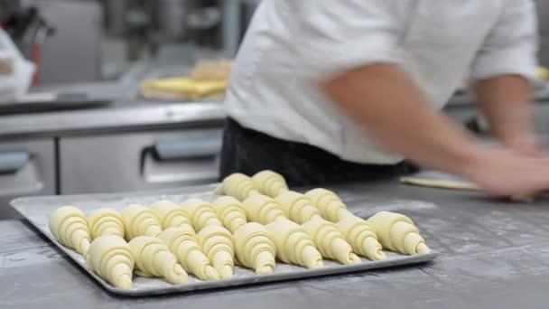 Cukrář válcování croissant těsto a dát pekáč v cukrárně.