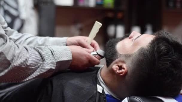 Holič, holení vousů pohledný vousatý muž s elektrický holicí strojek v holičství.