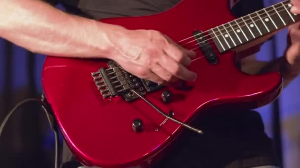 Musician playing red electric guitar on stage.