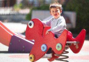 Cute happy baby boy with blond hair riding red spring rider or rocker on sunny summer day.