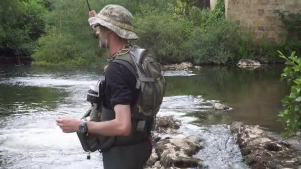 Halász halászata a folyón, horgászbot tartásával.