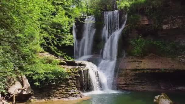 Idylický deštný prales vodopád, potok tekoucí v bujném zeleném lese.