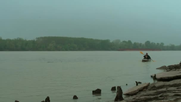 Man is swimming in a canoe near the shore