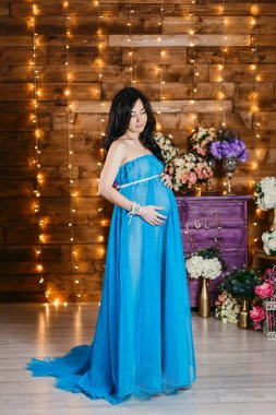 Beautiful pregnant brunette woman in a long silk blue dress standing at full length and looks at the belly in studio
