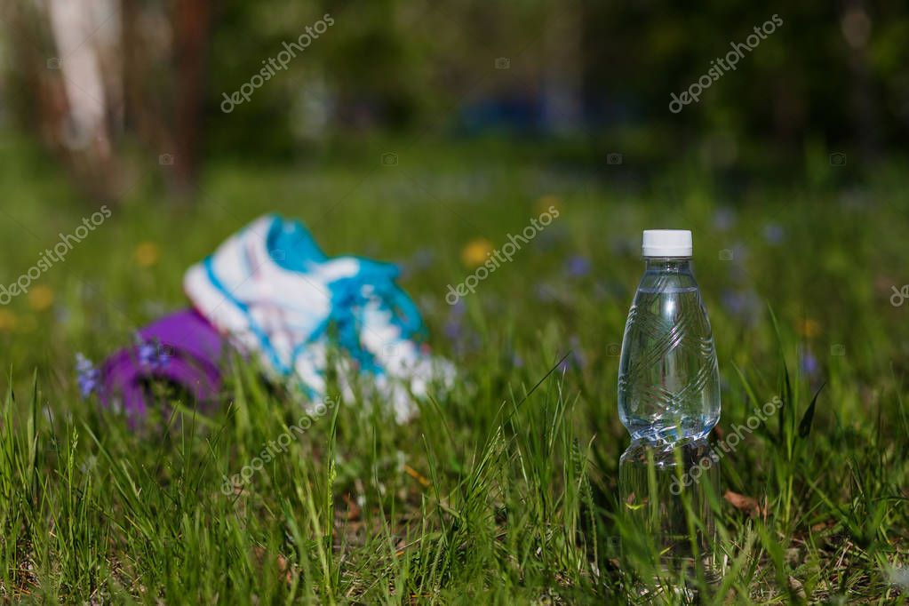 bottle of drinking water stands on the green grass outdoors in summer, running shoes