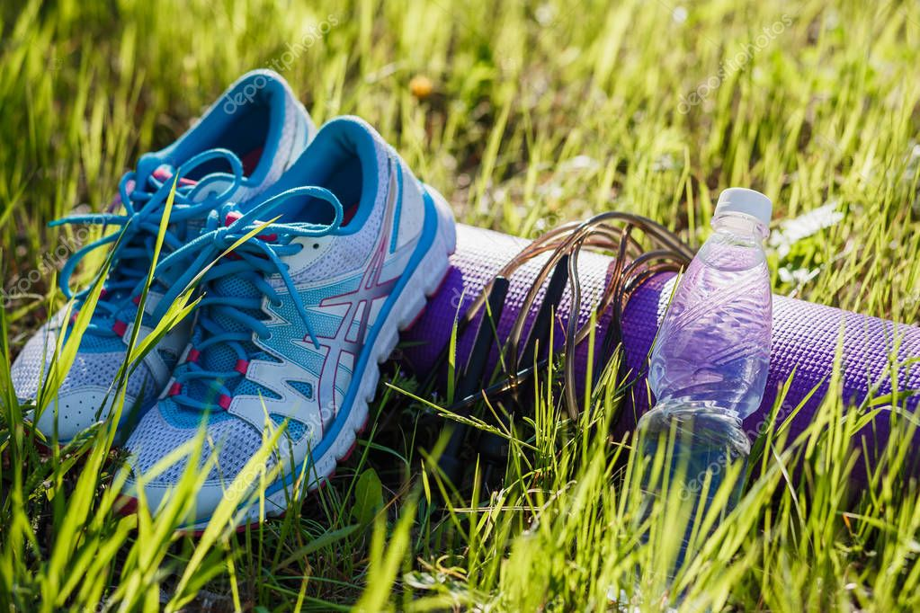 running shoes, water bottle and jump rope on green grass in summer, sport