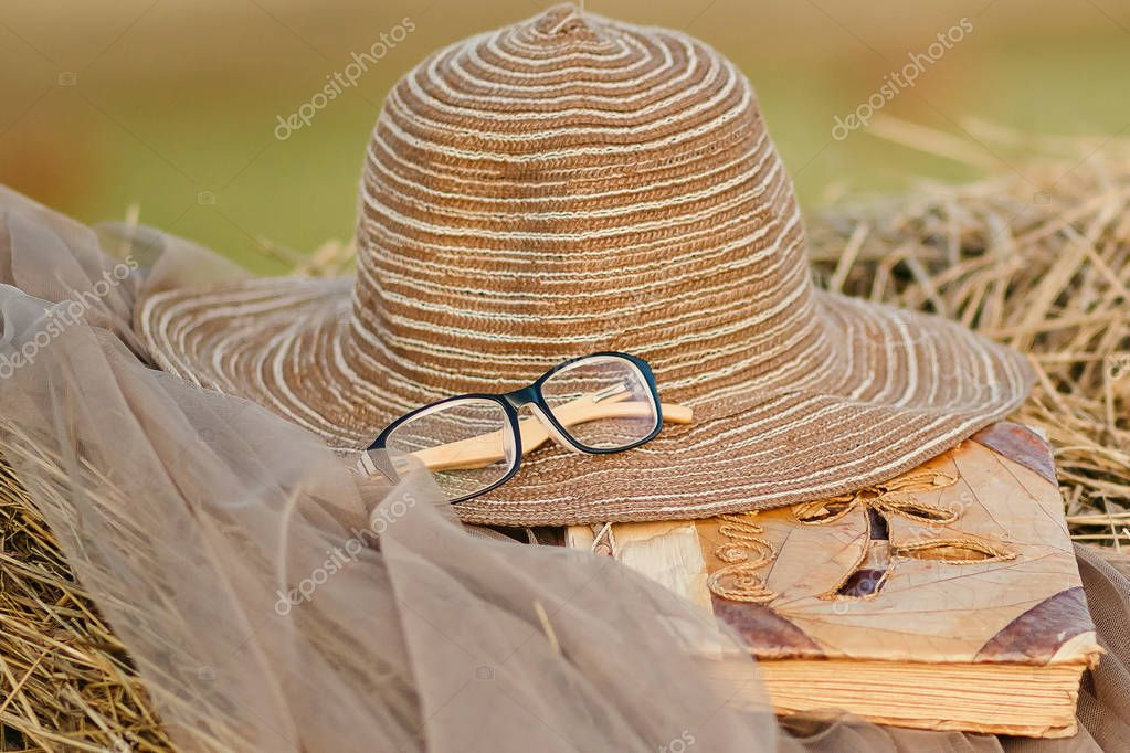 brown hat, glasses and book lying on straw outdoors