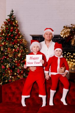 a man in a white shirt with two children in red costume on christmas eve