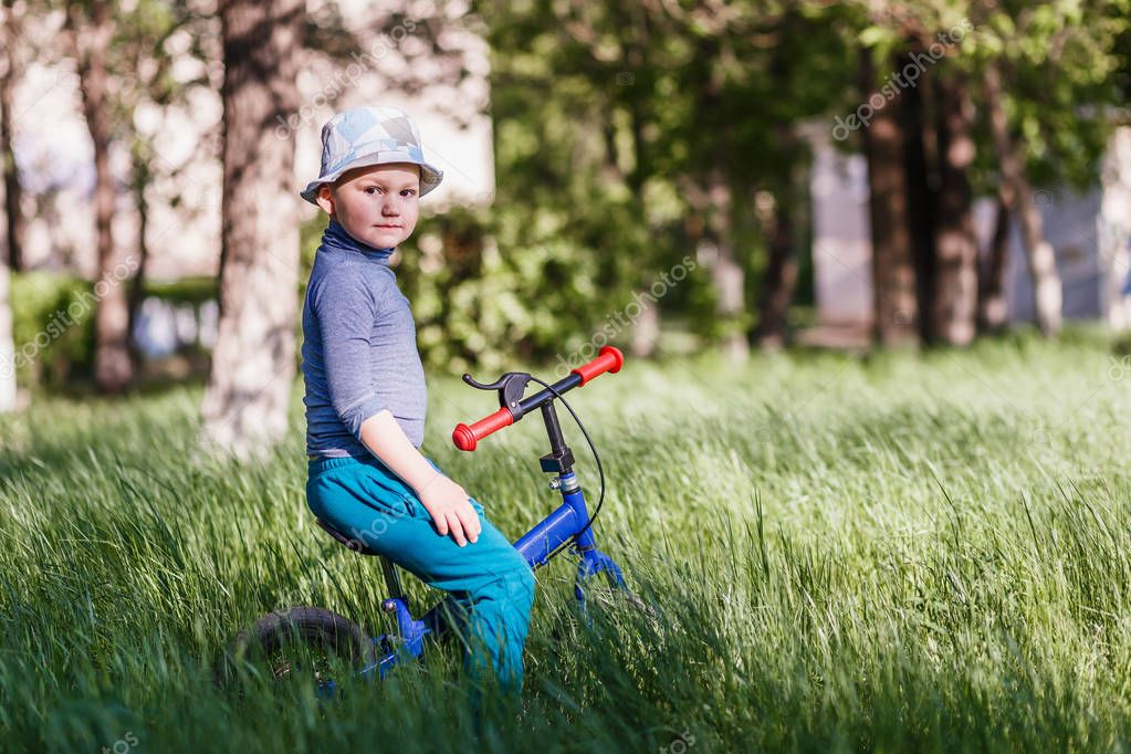 four-year-old boy in a hat sitting on a jogger in the green grass in the Park