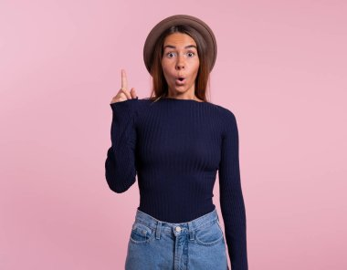Pretty woman in hat pointing finger up to copy space, isolated over pink background