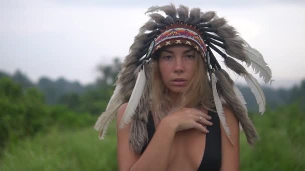 Hübsche Frau im indischen Kopfbedeckungen steht im offenen Bereich, blickt in die Kamera. Schwarzes Oberteil trägt. Porträt von schönen sexy im indischen Kopfbedeckungen in tropischer Umgebung