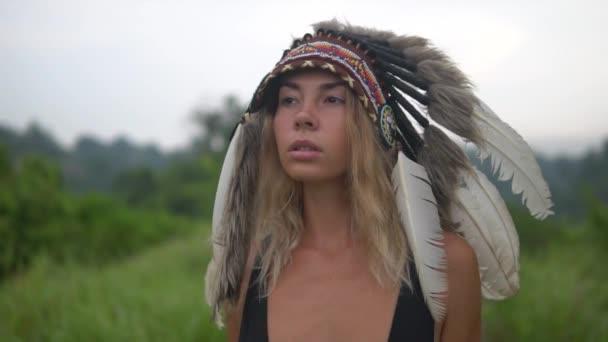 schöne junge Frau in indianischer Kopfbedeckung draußen. sexy Mädchen mit Kriegsmütze geht auf wildem Weg voran. graue Federn auf ihrem Kopf. Zeitlupe bewegt sich, schaut zur Seite.