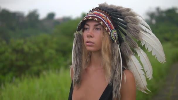 schöne Frau in indianischer Kopfbedeckung marschiert wild voran. Tolle Frau in schwarzem Badeanzug und Kriegsmütze geht vor die Kamera. Zeitlupe, blickt nach vorn.