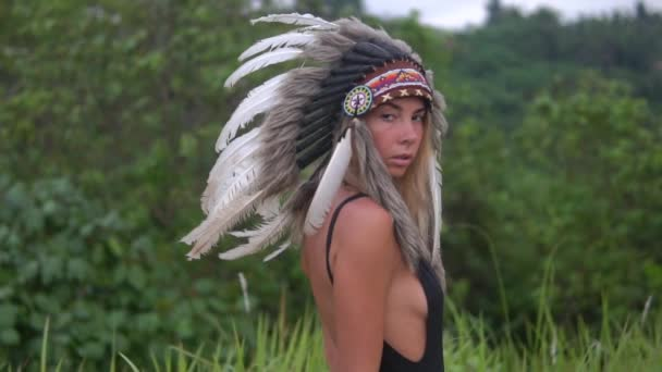 Beautiful young woman in black looks in camera, standing on road to jungle, wears traditional Indian headdress with feathers, camera floats around in slow motion