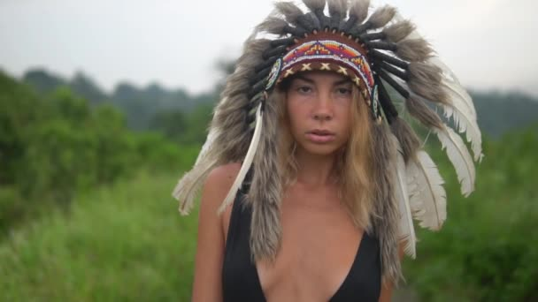 Fiatal modell megy fel a kamera. Karcsú nő indiai ruha és fekete fürdőruha megy út közepette trópusi fák, lélegzetelállító szőke lány warpath