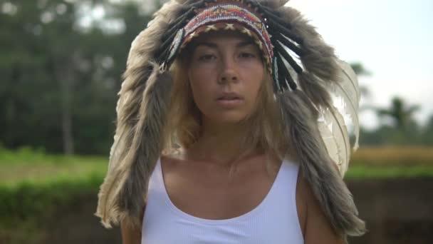 Nahaufnahme und Zeitlupenvideo eines blonden Modells in indischer Kriegsmütze,. schönes Mädchen mit Federkopfschmuck von Indianern, die im tropischen Wald spazieren gehen.