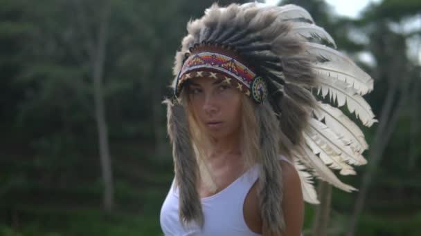 attraktives Model in traditioneller Kopfbedeckung mit grauen Federn steht auf einer Holzbrücke irgendwo in den Tropen, junge Frau in weißem Top und indischer Kriegsmütze vor dem Regenwald