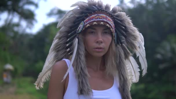 Porträt der jungen Femme in Zeitlupe, süßes Model mit Kopfschmuck und Federn, posiert wunderschön mit Dschungel im Hintergrund.