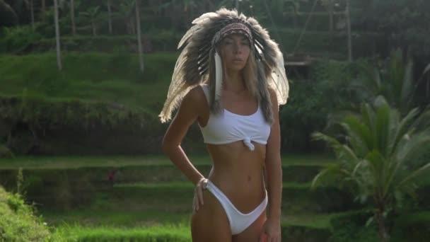 Zeitlupen-Shooting junger Models im weißen Bikini und indianischer Kopfbedeckung aus Federn, steht in schöner Pose, hinter ihr liegt tropischer Wald