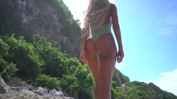 Cute girl in bikini walks under a rock, long blond hair fluttering in the wind, charming tattoo on her leg, summer day outdoors, slow motion and underside view