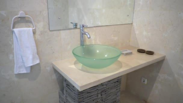 Umyvadlo v koupelně, na zdi visí velké zrcadlo, umyvadlo moderního skla, celou koupelnu zdobí světle mramor
