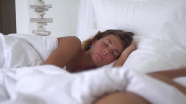 Fiatal nő alszik békésen, egy lágy ágy, édes reggeli álom, egy szelíd fehér takaró, fiatal pár aludni a kényelmes ágyban alatt