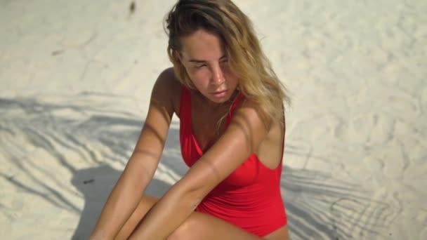 Atraktivní štíhlá blondýnka opálený je izolované na bílém písku, dospělé děvče v červených plavkách pózuje ve stínu stromu, ruce na kolenou, hledí do kamery