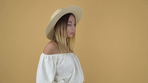 wunderschöne Blondine in weißen Bluse und posiert mit Strohhut hob linke hand