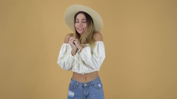 pretty young woman in straw hat, white shirt and jeans, presses hands to chest